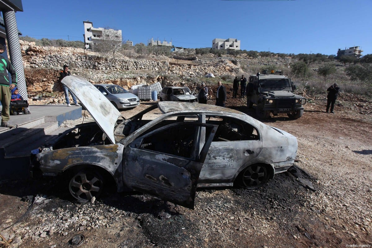 Palestinians inspect the damage done to their cars after settlers set fire to them in the West Bank on 20 December 2019 [Nedal Eshtayah/Anadolu Agency]