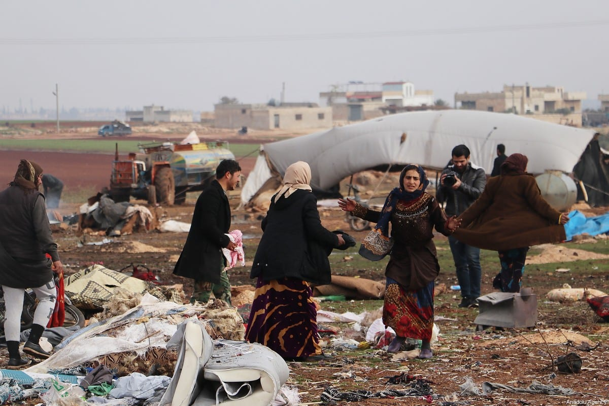Syrian citizens who were affected by attacks carried out by Russian warplanes over Saraqib district are seen, collecting their usable belongings, in the de-escalation zone of Idlib, Syria on 24 December 2019. [Hüseyin Fazıl - Anadolu Agency]