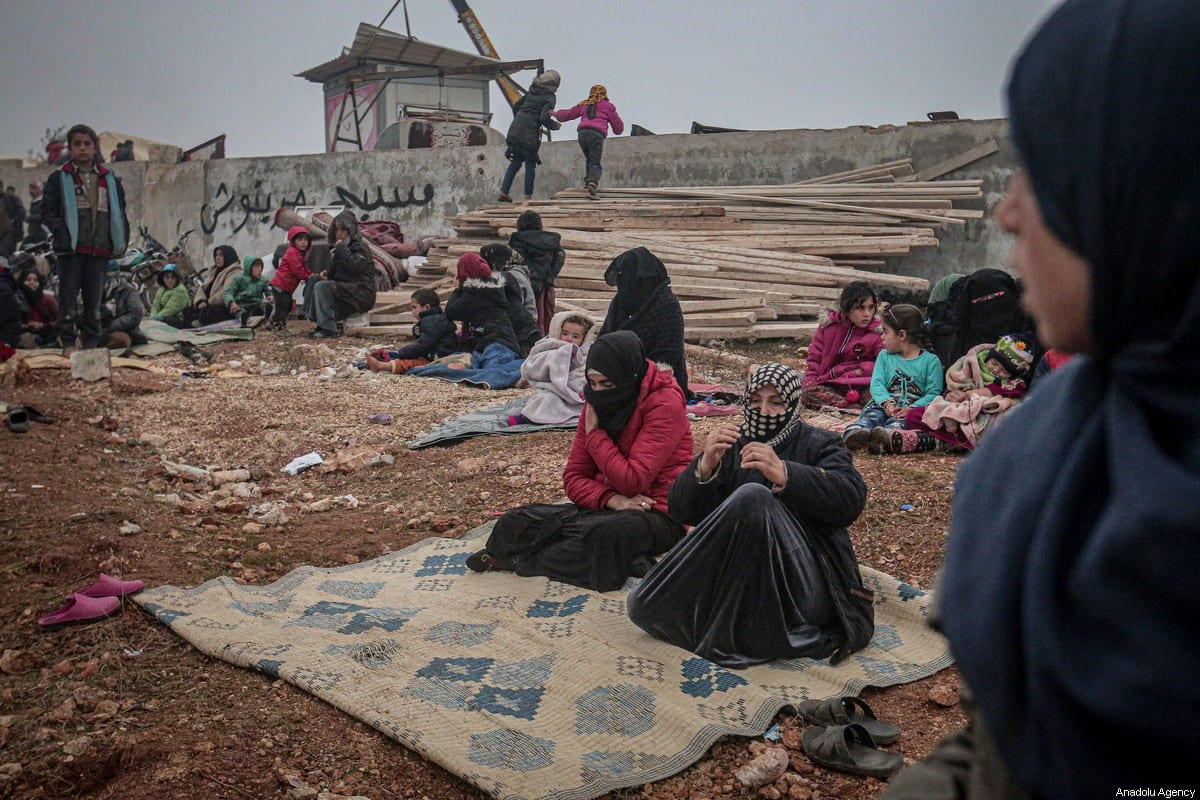 Syrians are seen with their belongings who have been forced to displace due to the ongoing attacks carried out by Assad regime and Russia, during winter season at makeshift tent area in Harbanos town of Idlib, Syria on 24 December 2019. [Muhammed Said - Anadolu Agency]