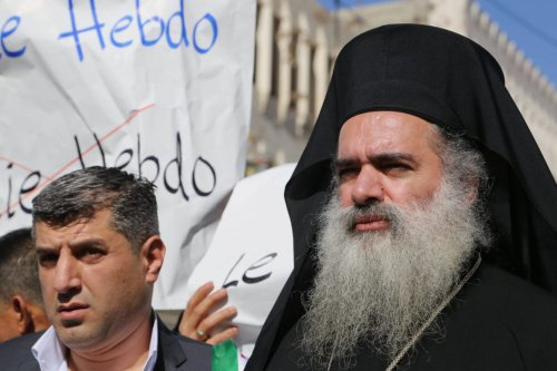 Bishop Atallah Hanna with Palestinian men take part in a protest against satirical French weekly magazine Charlie Hebdo's cartoons of the Prophet Mohammad, in the West bank city of Hebron on 22 January 2015. [Muhesen Amren-Apaimages]