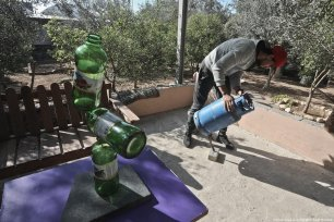 Palestinian Muhammad Al-Shanbari applies physics to art by balancing items on top of each other in Beit Hanoun, Gaza [Mohammed Asad/Middle East Monitor]
