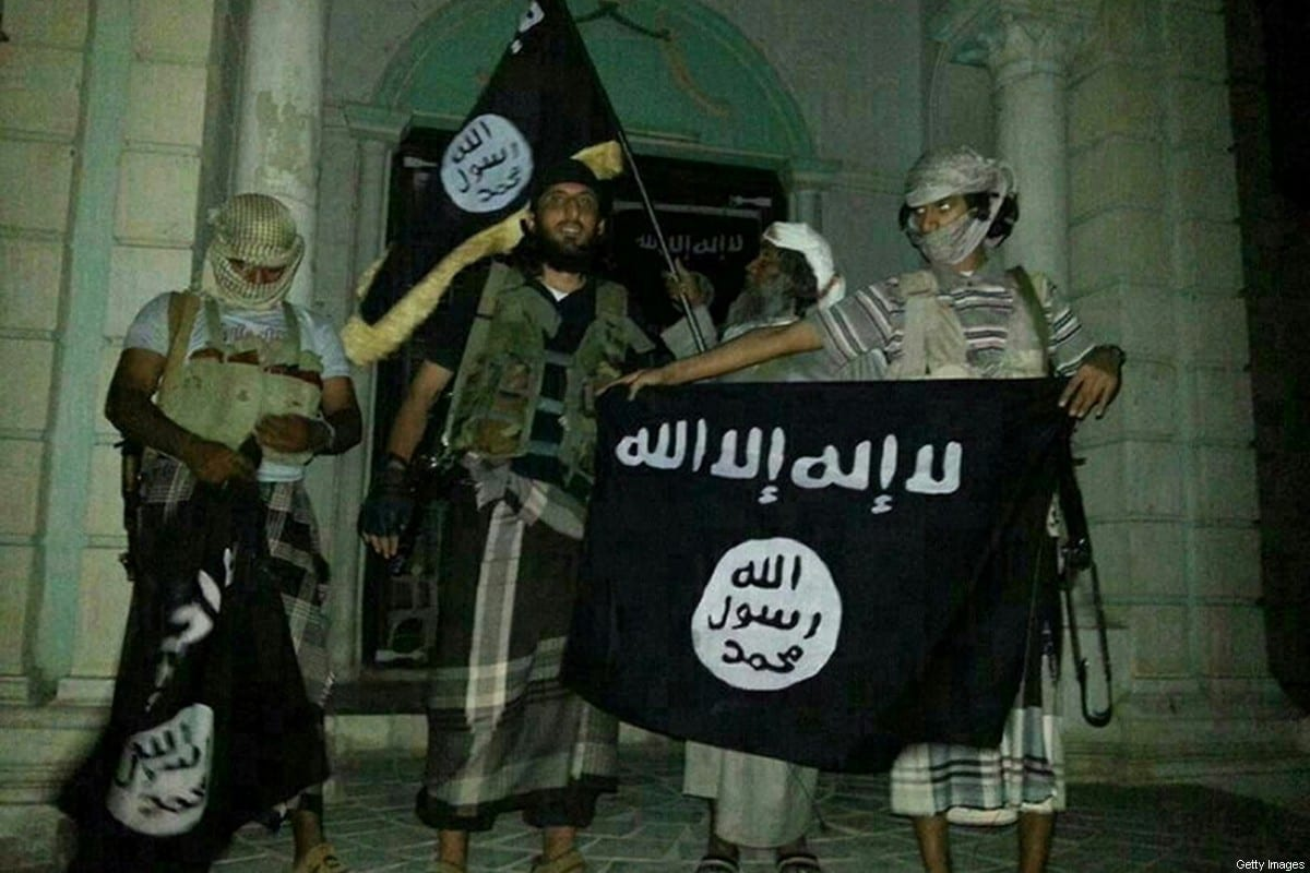 A picture taken with a mobile phone early on May 24, 2014 shows Al-Qaeda militants posing with Al-Qaeda flags in Yemen om 24 May 2014 [AFP/Getty Images]