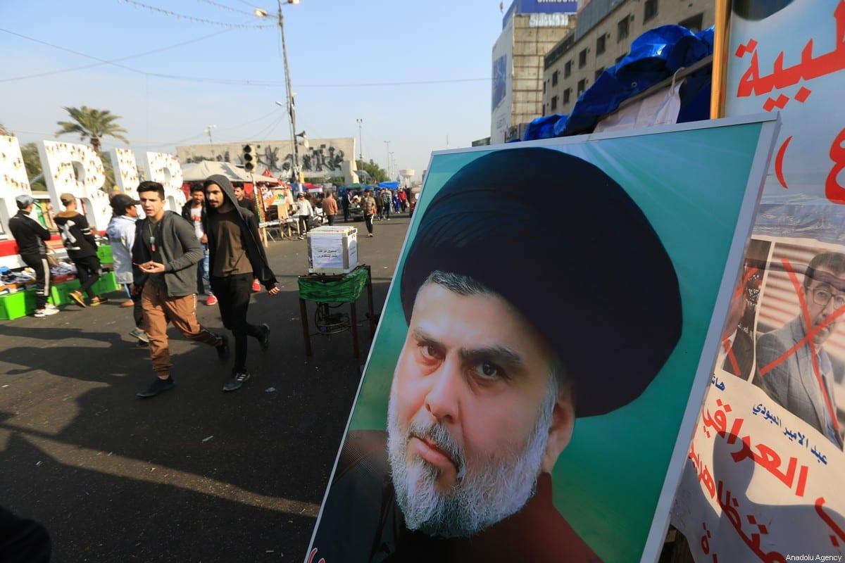 Poster of Sadrist Movement Leader Muqtada al-Sadr is seen as Iraqi demonstrators gather at Tahrir Square in Baghdad, Iraq on 3 January 2020 [Murtadha Sudani/Anadolu Agency]