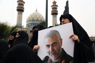 An Iranian woman carries an image of Iranian Revolutionary Guards' Quds Force commander Qasem Soleimani, who was killed by a US airstrike in the Iraqi capital Baghdad, during an anti-US rally to protest the killing at Palestine Square in the capital Tehran, Iran on January 4, 2020 [Fatemeh Bahrami / Anadolu Agency]