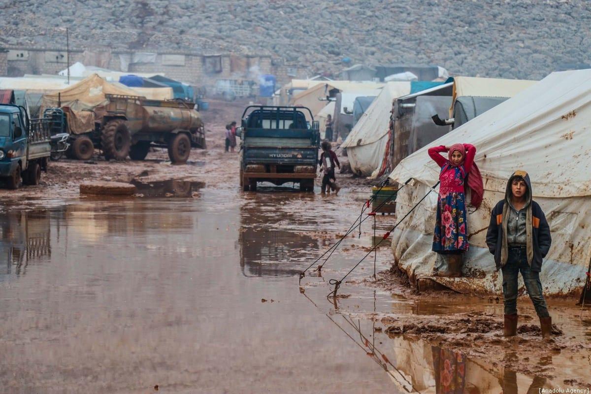 Syrian children are seen at muddy ground at Sarut Camp in Sarmada district of Idlib, Syria on 6 January 2020. [Erdal Türkoğlu - Anadolu Agency]