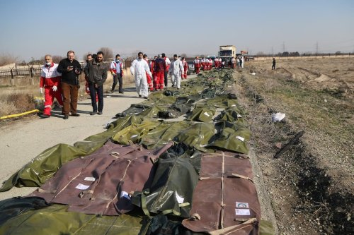Dead bodies of passengers are brought from the site by search and rescue team members after a Boeing 737 plane belonging to a Ukrainian airline crashed near Imam Khomeini Airport in Iran just after takeoff with 180 passengers on board in Tehran, Iran on 8 January 2020. [Fatemeh Bahrami - Anadolu Agency]