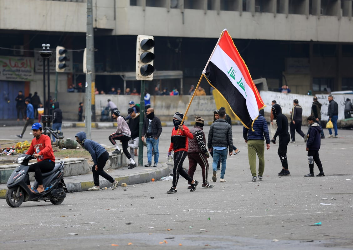 Anti-government demonstrator throw stones in response to security forces following their intervention at Tahrir Square in the centre of the Iraqi capital Baghdad on 25 January 2020. [Murtadha Al-Sudani - Anadolu Agency]