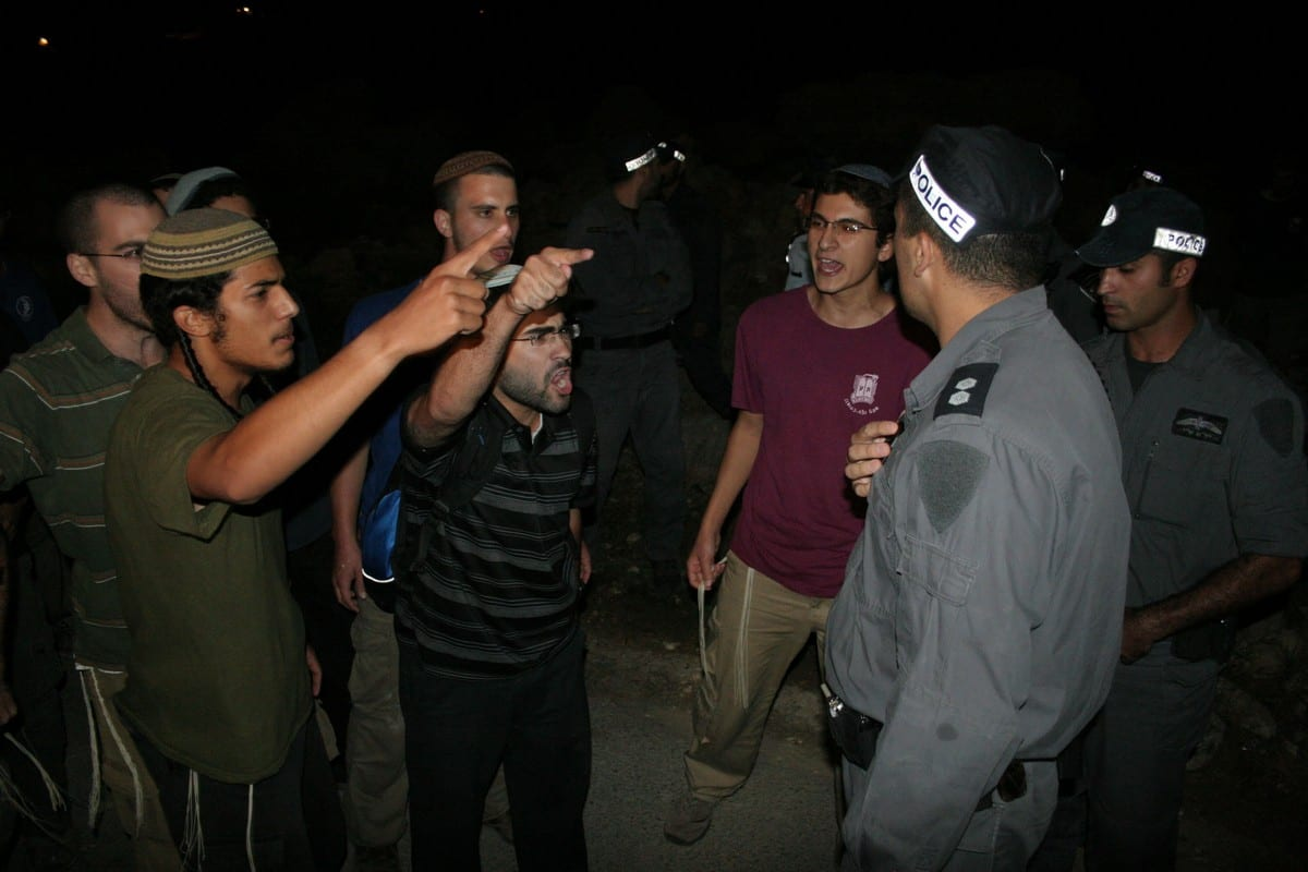 Israeli settlers express their anger in front of Israeli policemen in West Bank 31 August 2018 [Mamoun Wazwaz/Apaimages]
