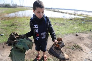 A Palestinian boy with muddy shoes after Israeli forces opened rainwater stores allowing water to flood Gaza on 15 January 2020 [Mohammed Asad/Middle East Monitor]
