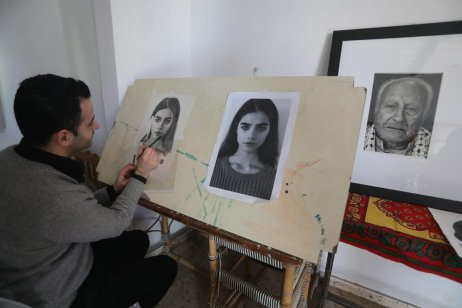 Palestinian Adam Shehata works with pencils to make almost lifelike portraits in black and white, 24 January 2020 [Mohammad Asad/Middle East Monitor]