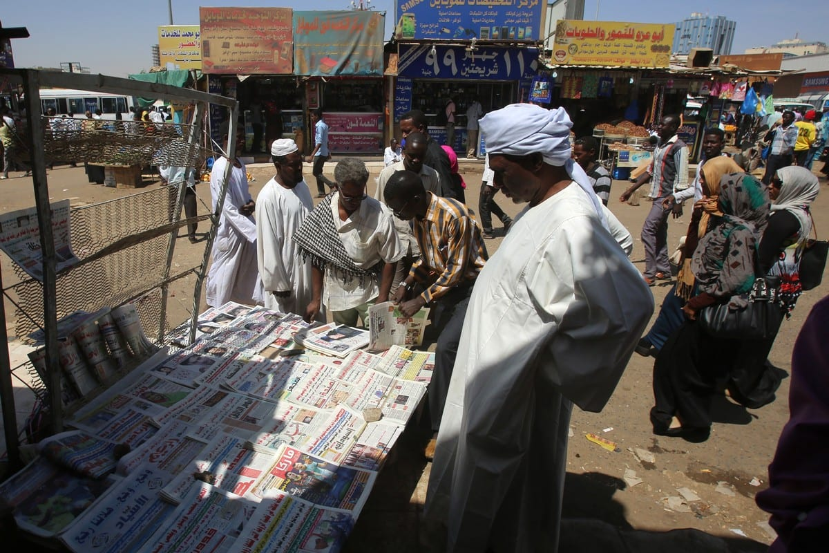 Sudanese men buy newspapers in the capital Khartoum on 24 February 2015 [ASHRAF SHAZLY/AFP/Getty Images]