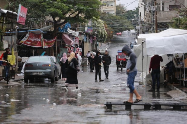 Palestinians are caught in the rain in Gaza on 9 January 2020 [Mohammed Asad/Middle East Monitor]