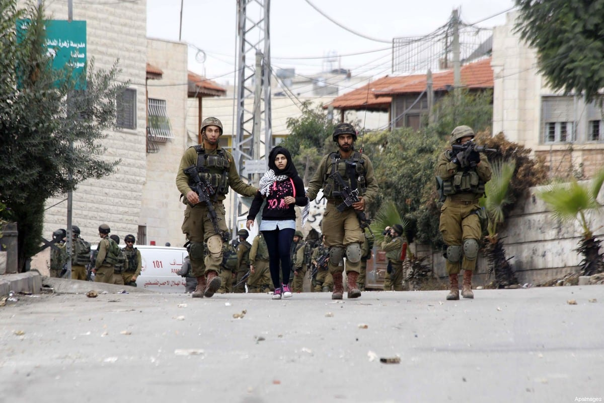 Israeli soldiers detain a Palestinian school girl following clashes with Palestinian protesters in the village of Beit Ummar near the southern West Bank city of Hebron on October 8, 2015 [ Muhesen Amren / ApaImages]