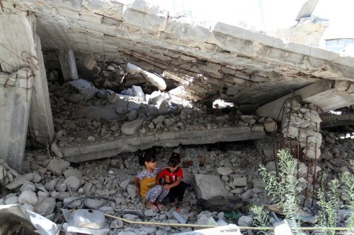 Palestinian girls play on the rubble of a house, which was destroyed during the 50-day war between Israel and Hamas militants in the summer of 2014, in Rafah in the southern Gaza Strip on 29 July, 2015 [Abed Rahim Khatib/ApaImages]