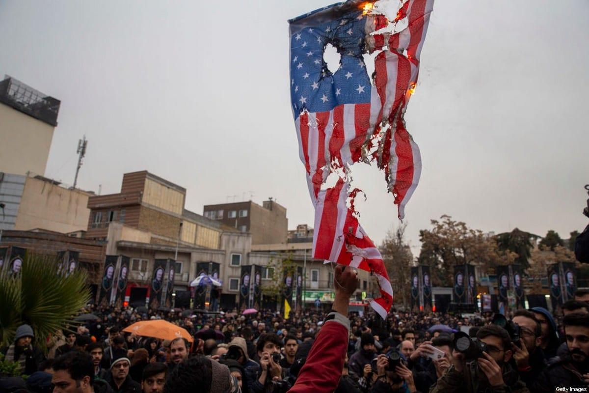 Iranians burn US and Israeli flags during an anti-US protest over the killings during a US air strike of Iranian military commander Qasem Soleimani and Iraqi paramilitary chief Abu Mahdi al-Muhandis on 4 January 2020 in Tehran, Iran. [Majid Saeedi/Getty Images]
