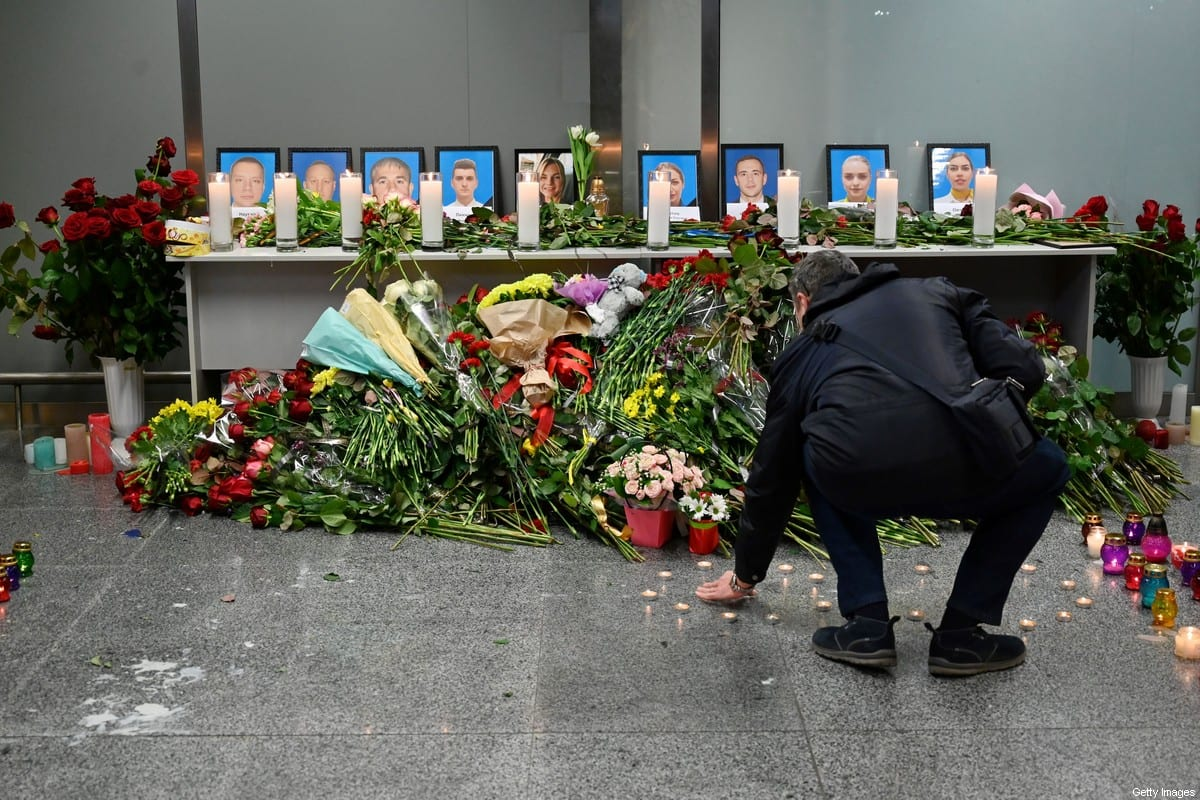 A man seen in front of a memorial for the victims of the Ukraine International Airlines Boeing 737-800 crash in the Iranian capital Tehran, at the Boryspil airport outside Kiev on January 8, 2020 [SERGEI SUPINSKY/AFP via Getty Images]