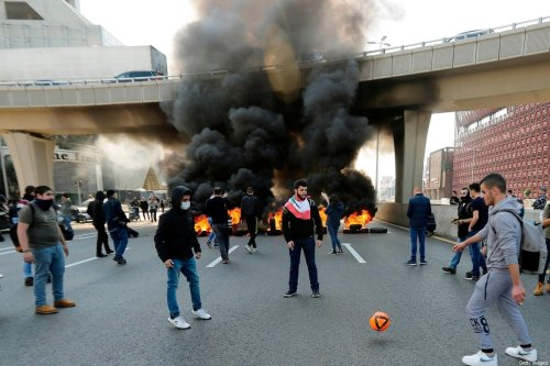 Lebanese anti-government protesters play football near a burning roadblock during a demonstration in Jal el-Dib area on the northern outskirts of the Lebanese capital Beirut on January 14, 2020. [JOSEPH EID/AFP via Getty Images]