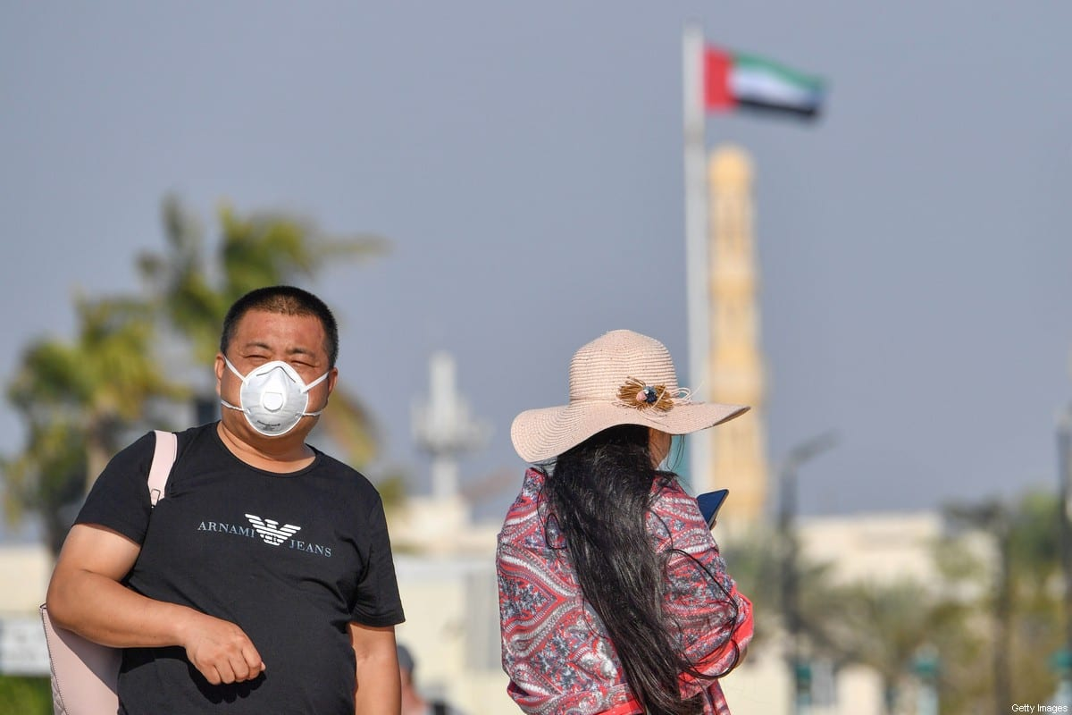 A Tourist wearing a surgical mask is pictured next to Burj in Dubai on January 29 2020 [GIUSEPPE CACACE/AFP via Getty Images]
