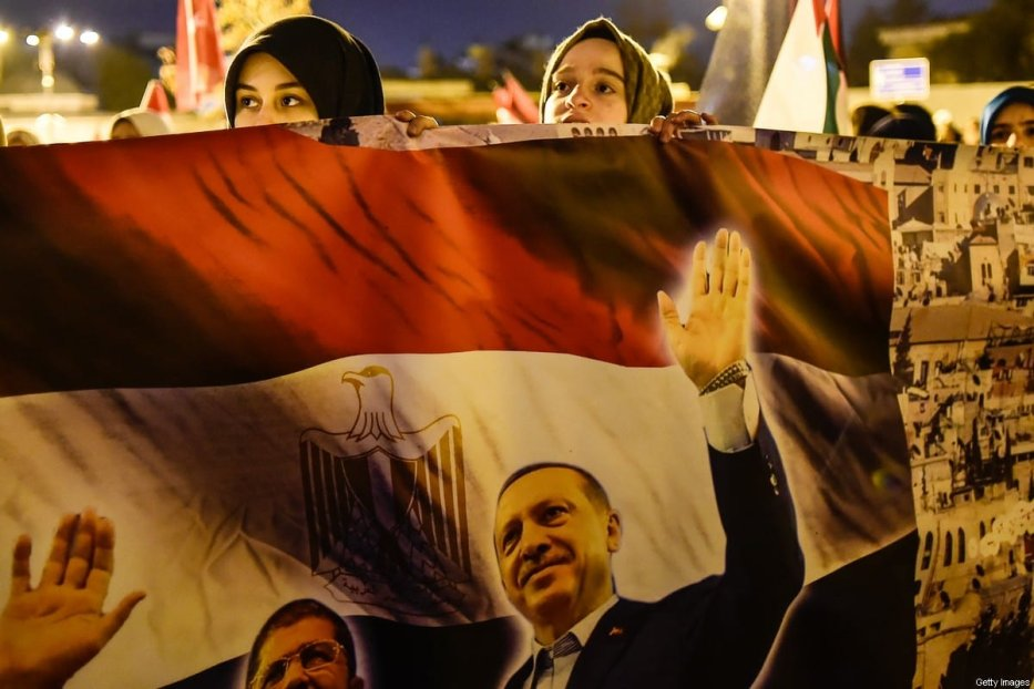 Protesters hold a poster with Turkish President Recep Tayyip Erdogan and Egypt's former president Mohamed Morsi during a demonstration against the US and Israel at Fatih Mosque in Istanbul on December 6, 2017. [YASIN AKGUL/AFP via Getty Images]
