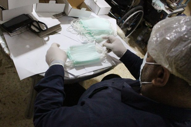 Palestinian workers produce face masks at a shoe factory in the West Bank city of Hebron on March 14, 2020 amid the spread of coronavirus. The factory, under the supervision of the Palestinian Standards and Measurements Institute, is set to produce between 10 to 15 thousand facial masks on daily basis to provide the local market with the highly-demanded mask considered vital in fighting the spread of coronavirus [Mosab Shawer / ApaImages]
