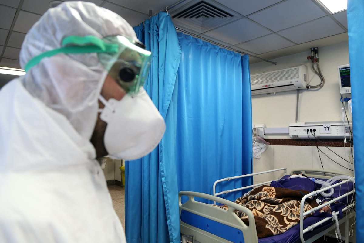 A health officer, wearing a mask and special protective suit, takes care of a patient infected by the coronavirus (COVID-19) at a hospital in Tehran, Iran on 2 March 2020. [Fatemeh Bahrami - Anadolu Agency]