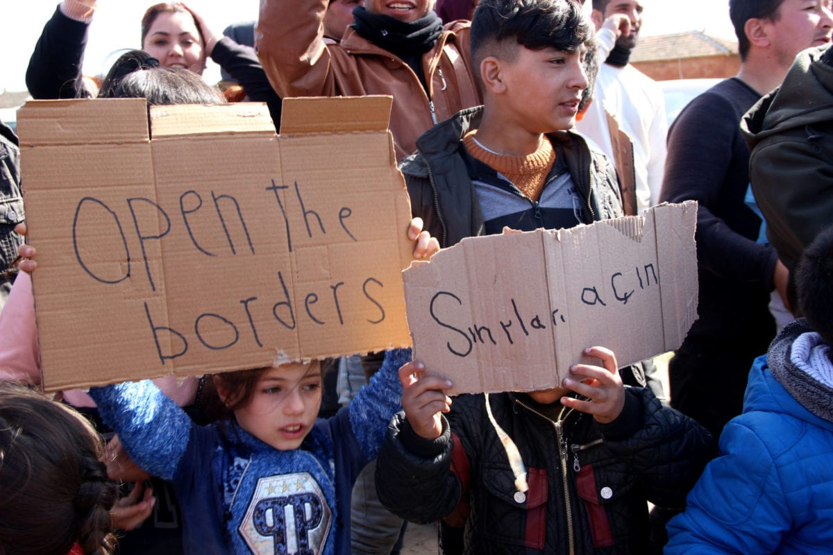 "Irregular migrants hold placards reading ""open the border gates"" as they continue to wait in Edirne, Turkey to reach Greece on 3 March 2020. [Gökhan Zobar - Anadolu Agency]"