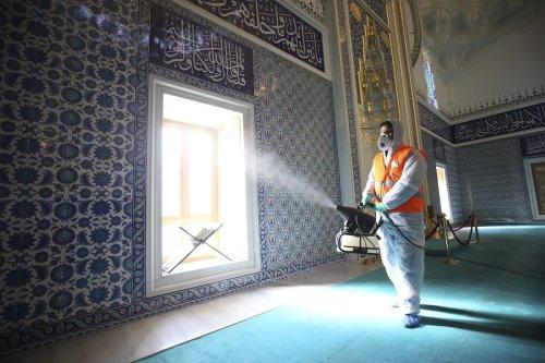 A health officer wearing protective suit sprays disinfectant at a Melike Hatun Mosque ahead of Friday prayer as a precaution against the coronavirus in Ankara, Turkey on 13 March 2020. [Doğukan Keskinkılıç - Anadolu Agency]