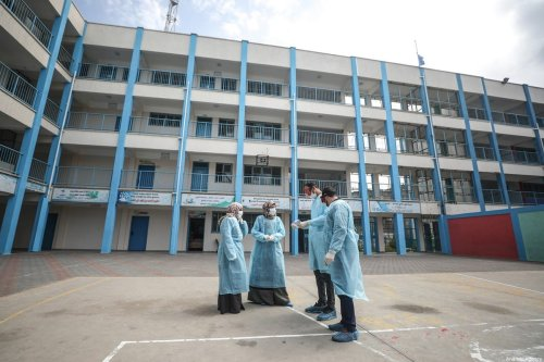 Healthcare workers are seen at the yard of a school which is turned by the United Nations Relief and Works Agency for Palestine Refugees (UNRWA) into a clinic for patients with respiratory system disorders as a precaution against the coronavirus (COVID-19) in Gaza City, Gaza on March 18, 2020. [Ali Jadallah - Anadolu Agency]