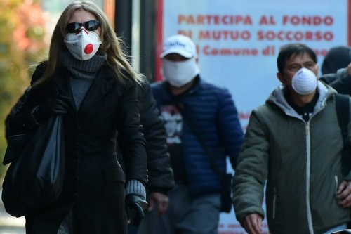 Italians seen wearing protective masks during the coronavirus outbreak on March 18, 2020 in Milan, Italy [Pier Marco Tacca / Anadolu Agency]