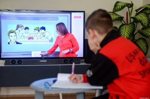 A primary school student watches his lecture from the TV at his house within the distance education program, on 23 March 2020 in Usak, Turkey. [Orhan Fatih Doğan - Anadolu Agency]