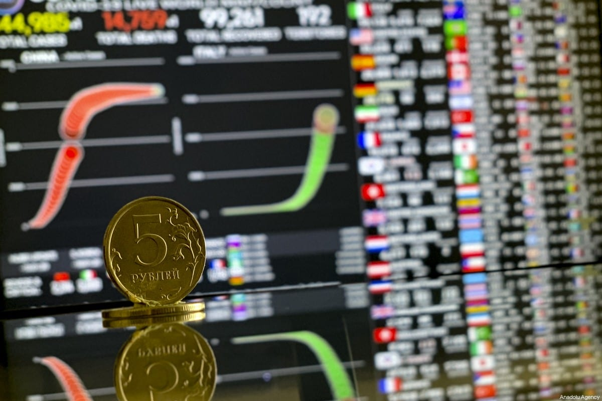 A Russian coin is seen with a stock market board in Moscow, Russia on 23 March 2020 [Sefa Karacan/Anadolu Agency]