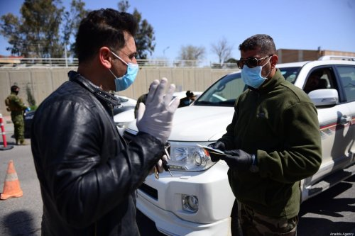 A security force controls the documents of a citizen at a checkpoint after the curfew was declared as part of precautions against the coronavirus (COVID-19), in Sulaymaniyah, Iraq on 23 March 2020. [Fariq Faraj Mahmood - Anadolu Agency]