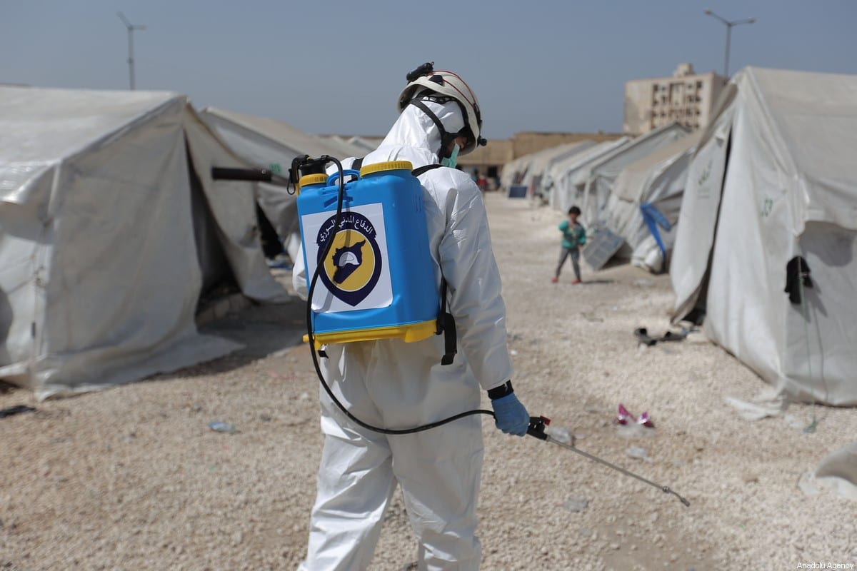 Members of the Syrian Civil Defence (White Helmets) disinfect tents inhabited by families as a preventive measure against coronavirus (Covid-19) pandemic in Idlib, Syria on 24 March 2020 [Muhammed Said/Anadolu Agency]