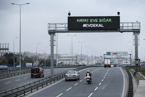 """Cars go under a traffic information sign declaring """"Life fits inside the home - Stay at Home"""" as people adhere to government advice on social distancing as a preventive measure against the spreading of coronavirus (Covid-19) in Istanbul, Turkey on 26 March 2020. [Elif Öztürk - Anadolu Agency]"""
