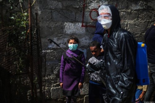 A group of volunteer youth carry out disinfection works at a refugee camp as part of coronavirus (Covid-19) pandemic precautions, in Khan Yunis, Gaza on March 29, 2020 [Mustafa Hassona / Anadolu Agency]