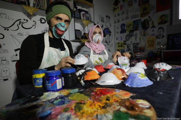 Palestinian artists Samah Saeed and Durham Krickk paint on face masks in order raise awareness on coronavrius in Gaza, 25 March 2020 [Mohammed Asad/Middle East Monitor]