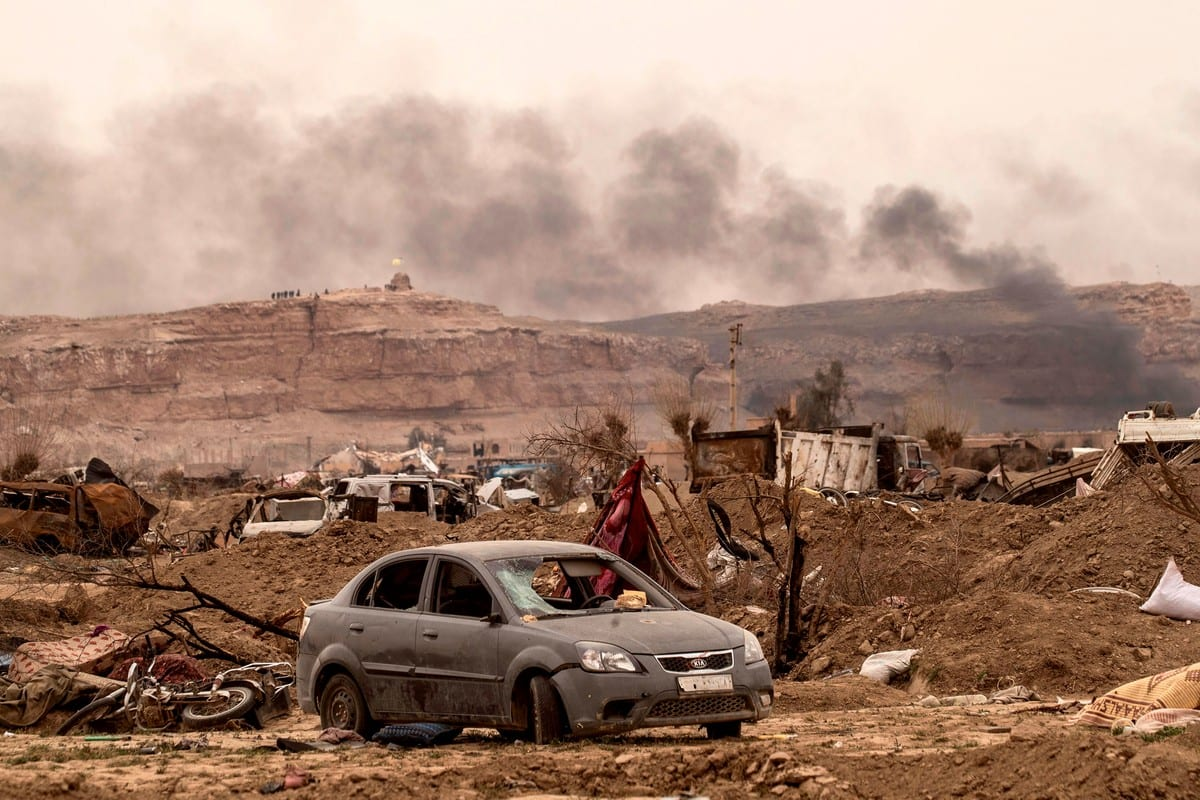 Smoke rising behind destroyed vehicles and damaged buildings in Syria's eastern Deir Ezzor province near the Iraqi border on 24 March 2019 [DELIL SOULEIMAN/AFP/Getty Images]
