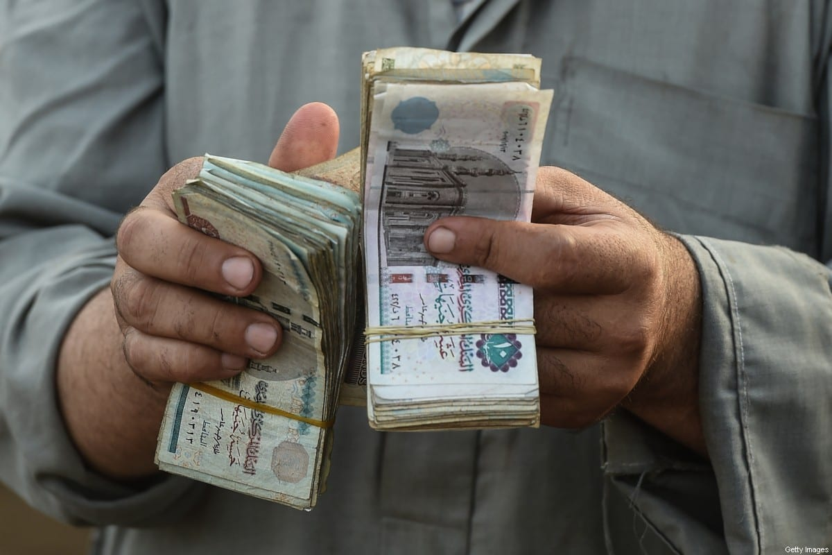 An Egyptian cattle trader counts his money at the Ashmun market in Egypt's Menufia Governorate on August 15, 2018, [MOHAMED EL-SHAHED/AFP via Getty Images]