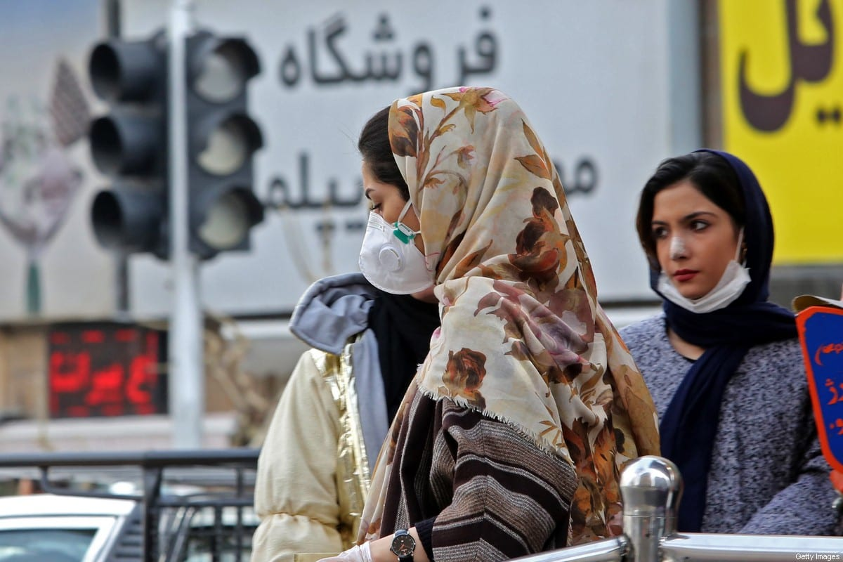 "Women wearing protective masks walk along a street in the Iranian capital Tehran on February 24, 2020. - Iran's government vowed on February 24 to be transparent after being accused of covering up the deadliest coronavirus COVID-19 outbreak outside China as it dismissed claims the toll could be as high as 50. The authorities in the Islamic republic have come under mounting public pressure since it took days for them to admit to ""accidentally"" shooting down a Ukrainian airliner last month, killing 176 people. Iran has been scrambling to contain the outbreak since it announced the first two deaths in the holy city of Qom on February 19. (Photo by ATTA KENARE / AFP) (Photo by ATTA KENARE/AFP via Getty Images)"
