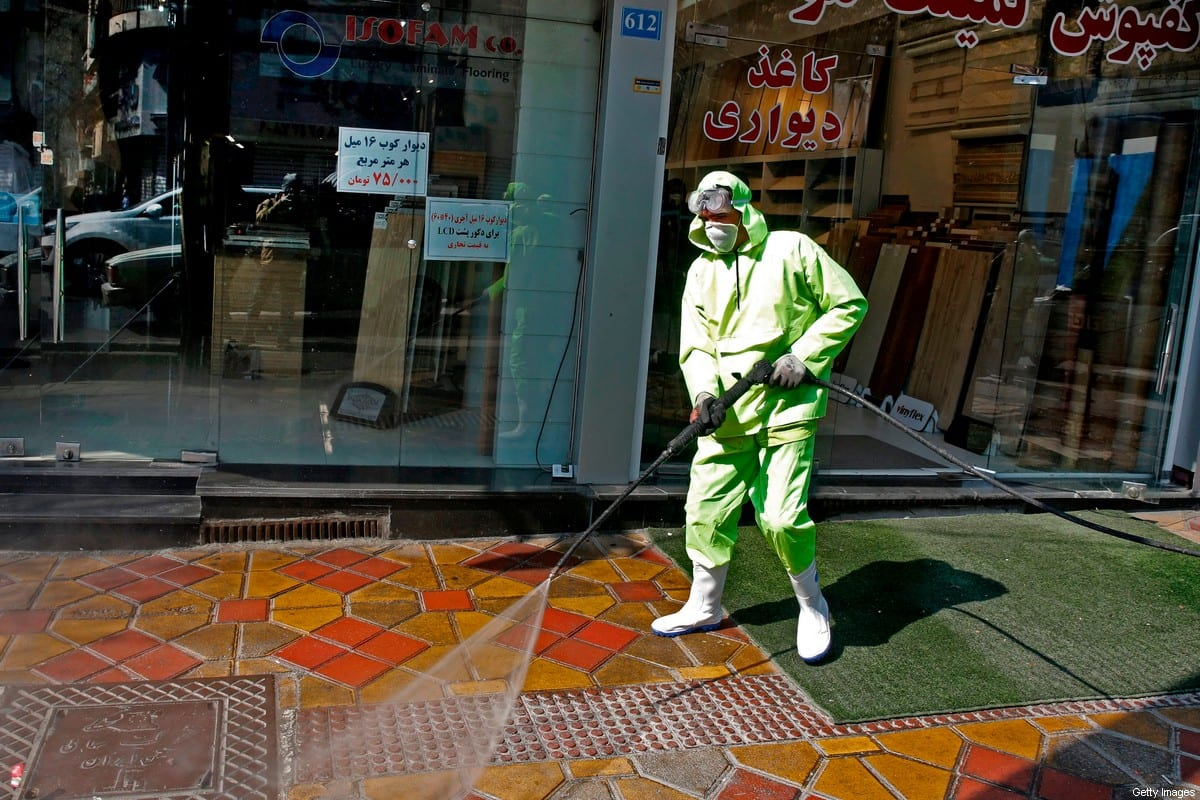 Iranian fire fighters and municipality workers disinfect a street in the capital Tehran for corona virus COVID-19 on 5 March 2020. [STR/AFP via Getty Images]