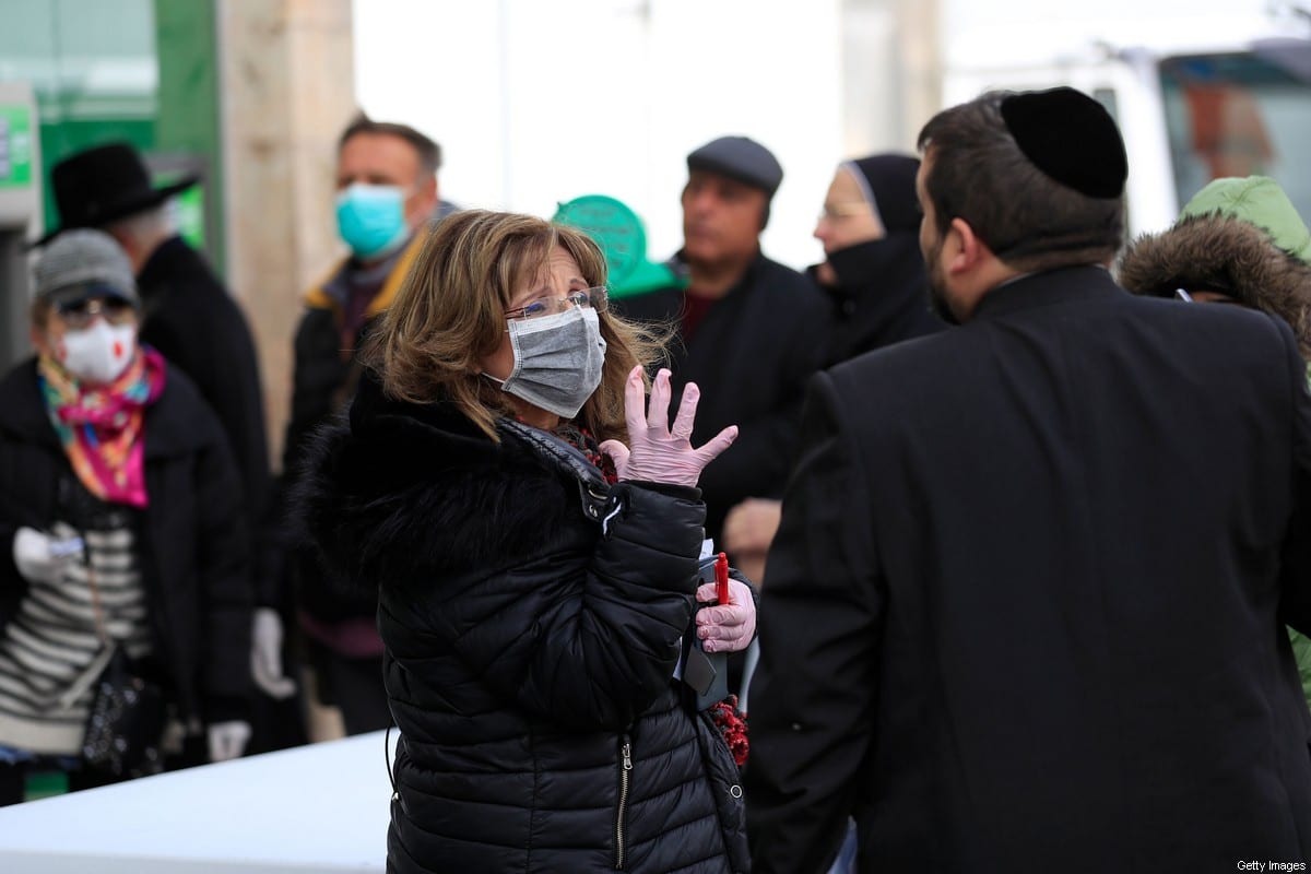 People wearing protective face masks during the Covid-19 pandemic wait in line to enter a bank in Jerusalem on March 19, 2020 [EMMANUEL DUNAND/AFP via Getty Images]