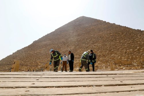 Egyptian municipality workers disinfect the Giza pyramids necropolis on the southwestern outskirts of the Egyptian capital Cairo on March 25, 2020 as protective a measure against the spread of the coronavirus COVID-19. [KHALED DESOUKI/AFP via Getty Images]