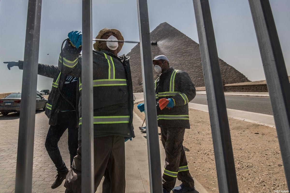 Egyptian municipality workers disinfect the Giza pyramids as protective a measure against the spread of the coronavirus on 20 March 2020 [KHALED DESOUKI/AFP/Getty Images]