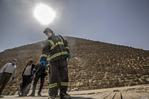 Egyptian municipality workers disinfect the Giza pyramids necropolis on the southwestern outskirts of the Egyptian capital Cairo on March 25, 2020 as protective a measure against the spread of the coronavirus COVID-19 [KHALED DESOUKI / AFP via Getty Images]