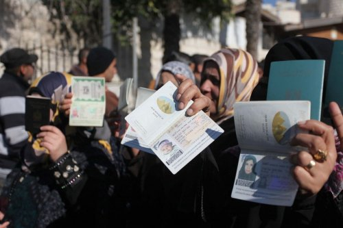 Palestinian women hold their passports during a protest demanding for the opening of Rafah crossing border in Gaza 31 December 2014 [Ashraf Amra/Apaimages]