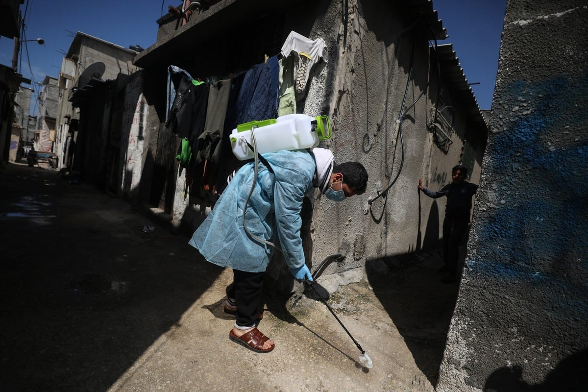 A volunteer carries out disinfection work as a precaution against the coronavirus (COVID-19) along the streets of Gaza City on 16 March 2020 [Ali Jadallah/Anadolu Agency]