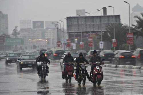 Egyptian men drive in the rain in Cairo, Egypt on 13 December 2013 [KHALED DESOUKI/AFP/Getty Images]