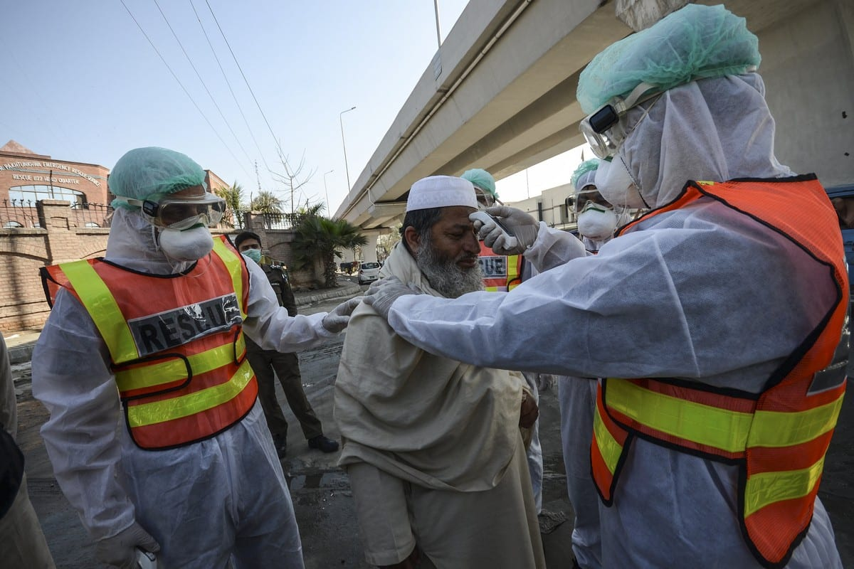 Pakistani rescue personnels check the body temperature of a man during a drill as a precaution against coronavirus in Peshawar, Pakistan on 2 March 2020 [H Ali/Anadolu Agency]