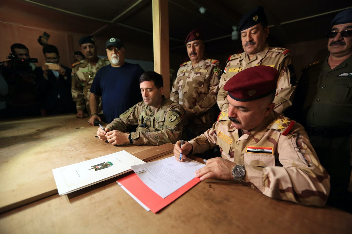 Commander of 32nd Brigade Ahmed Qasim (R) attends the US handover ceremony of al-Qaim military base, where has been used by US-led coalition troops, on the Iraq-Syria border in Iraq's Anbar province, west of Baghdad, on 19 March 2020. [Murtadha Al-Sudani - Anadolu Agency]