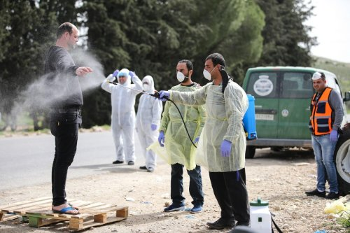 Workers spray disinfectant to Palestinian workers in Jerusalem, before they enter the West Bank through a checkpoint as part of precautions for the coronavirus (COVID-19) pandemic on 27 March 2020 [Mostafa Alkharouf/Anadolu Agency]